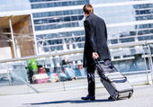 Business man walking with suitcase in the street — Stock Photo