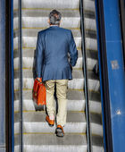 Business man taking the escalator to get to work — Stock Photo