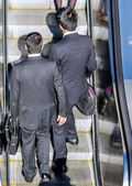 Business men taking the escalator to get to work — Stock Photo