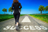 Running woman and Success word painted on asphalt — Stock Photo