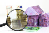 Euro bill House and expenses under magnifying glass — Stock Photo