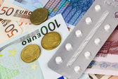 Medical pills and tablets in euro bank notes money — Stock Photo