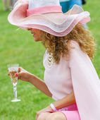 Elegant woman drinking with her beautiful hat — Stock Photo