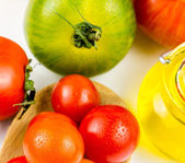 Varieties of colorful tomatos and olive oil — Stock Photo