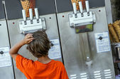 Child hesitating in front an ice machine — Stock Photo