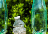 Three plastic bottles with one bottle crushed — Stock Photo