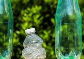 Three plastic bottles with one bottle crushed — Stock Photo