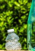 Two plastic bottles with one bottle crushed — Stock Photo