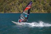 Windsurfer on mountain lake. — Stock Photo