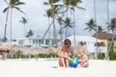Moeder en kleine dochter spelen op het strand — Stockfoto