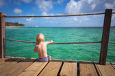 A small child sits on the edge of the pier — Stock Photo