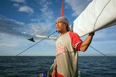 身份不明的年轻男性行一艘船在海中 — 图库照片