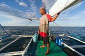 Jovem macho remar um barco no mar — Foto Stock
