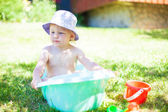 Little girl playing with the water on the grass — Stock Photo