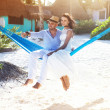 Couple sitting in a hammock on the beach — Stock Photo #37264679