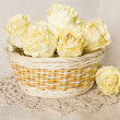 Dried roses in basket with doily — Stock Photo