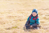 Child on dry grass (field) — Stock Photo