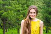 Smiling girl in pine park — Stock Photo