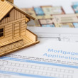 Stock Photo: House mortgage application with model house and construction pla