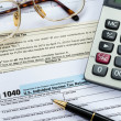 Stock Photo: Tax form with pen, calculator, and glasses taxation concept