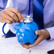 Stock Photo: Businessmuse stethoscope with piggy bank for financial health