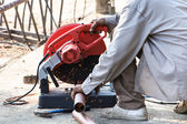 A craftman is cutting steel outdoor with a machine — Stock Photo