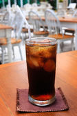 A glass of cola on a table — Stockfoto