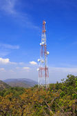 Communications tower on mountain with blue sky — Stock Photo