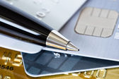 Pen on credit stack of cards — Stock Photo