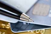 Pen on credit stack of cards low dept of field — Stock Photo
