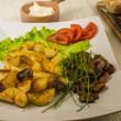 Mushrooms roasted with potatoes on the background of ingredients (vegetables) - Stock Photo