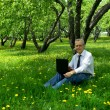 Men use the Internet in the summer on the nature - Stock Photo