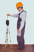 Foreman checks the quality of a laser level — Stock fotografie