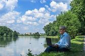 An elderly businessman is working the summer in the park using t — Stock Photo