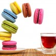 Stock Photo: Multi-coloured cakes makaroons fall towards cup of red tea