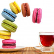 Multi-coloured cakes makaroons fall towards the cup of red tea — Stock Photo