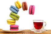 Multi-coloured cakes makaroons fall towards the cup of red tea — Fotografia Stock