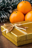 Orange mandarines and gold gift — Stock Photo