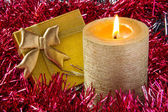 Gold candle with gift — Stock Photo