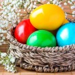 Colored painted eggs in a wattled basket with flowers - Stock Photo
