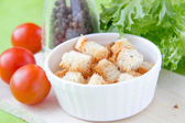Crouton in white ceramic cup — Stock Photo