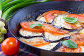 Roasted tomatoes, eggplant and cheese on pan with basil — Stock Photo