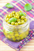 Tinned green peas in glass jar — Stock Photo