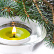 Green candle with flame and branch of Christmas tree — Stock Photo