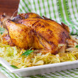 Roasted whole chicken with golden crust and garnish of stewed ca — Stock Photo