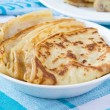 Ruddy russian pancakes folded triangle for shrovetide in bowl — Stock Photo
