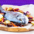 Baked whole fish dorada with grilled stew of roots — Stock Photo