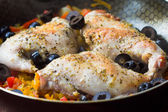 Fried ruddy leg of rabbit with vegetables, olives and herbs on f — Stock Photo