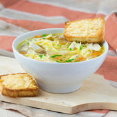 Chicken soup with noodles, carrots and cheese croutons — Stock Photo