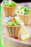 Salad tartar with herring, avocado, lettuce in tartlet, canapes — Stock Photo